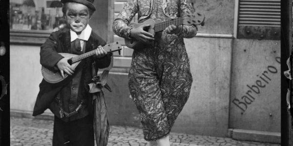 """Porque hoje é Carnaval... Fotografia de 1926 (Torre do Tombo), de dia de desfile de Carnaval em Lisboa. O pequeno Charlot transporta um 𝐛𝐚𝐧𝐝𝐮𝐫𝐫𝐢𝐧𝐡𝐨, instrumento bastante utilizado em Portugal, em tunas rurais e urbanas e tocatas populares entre o século XIX e o primeiro quarto do século XX. Com 4 ordens de cordas metálicas, é afinado em MI LÁ RÉ SOL (violino, bandolim) ou RÉ SI SOL RÉ (cavaquinho). A caixa tem apenas um bojo, piriforme; o braço é raso com o tampo, a escala tem doze trastes e as cravelhas são dorsais. A criança mascarada de Pierrot tem consigo um 𝐜𝐚𝐯𝐚𝐪𝐮𝐢𝐧𝐡𝐨 𝐝𝐞 𝟔 𝐜𝐨𝐫𝐝𝐚𝐬, um cordofone que se sente bastante confortável em ambientes festivos, lúdicos e profanos, do """"terreiro rural à taberna urbana"""". É considerado um instrumento muito completo, pois, apesar do tamanho é capaz de produzir em simultâneo ritmo, harmonia e melodia através das técnicas de rasgado. Tradicionalmente de 4 cordas metálicas, tem versões de 6 e 8 cordas, usadas sobretudo em grupos ou tunas, beneficiando do som mais poderoso. Fonte: Nuno Cristo Com a folia possível, boa terça-feira de Carnaval!"""
